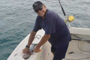 Commodore Chuck Gauthier chops up his piece of the wahoo. Photo: Karen Earnshaw
