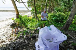 The Mieco Beach Yacht Club's Lanny Pirtle tosses a bottle into a waste collection bag at Enemanet Island. Photo: Mika Makelainen.